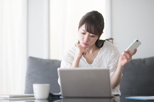 PCの前で悩む女性