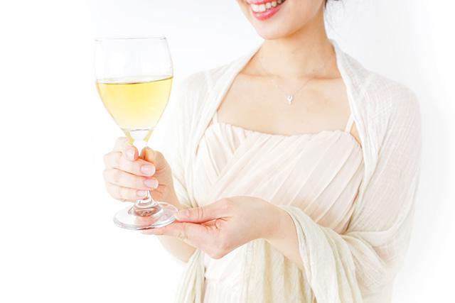 ワンピース姿でワインを持つ女性